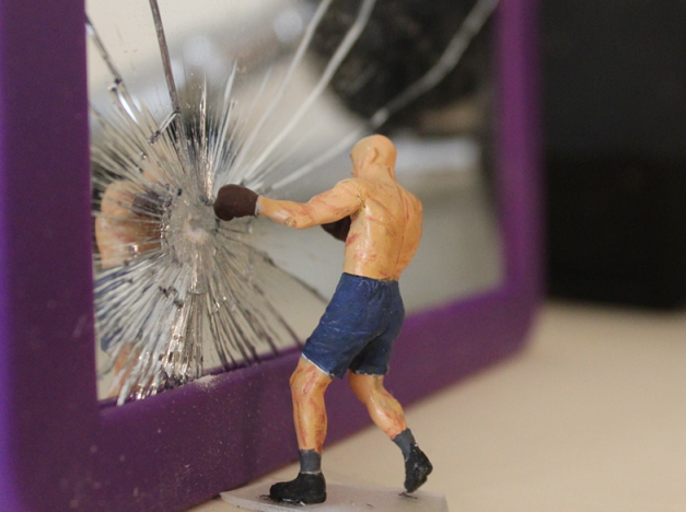 A boxer bashes his reflection in a mirror with his fist